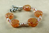 "Handcrafted lampork glass beads, Swarovski crystal pearls, sterling silver beads and sterling silver handcrafted clasp.  Warm orange with pale apricot. Fits a 6-3/4"" wrist. <br /> (ob3256)"