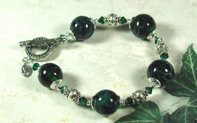 "Handcrafted lampork glass beads, Swarovski crystals, handcrafted sterling silver bead caps, beads  and clasp. The colors in this bracelet are very deep and very rich. Fits a 7-1/4"" wrist. <br /> (ob3844)"