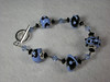 "Handcrafted lampwork glass beads, handcrafted sterling silver beadcaps and sterling silver clasp, Swarovski crystals, teensy French cut steel beads, circa 1900. Periwinkle blue with black.  Fits a 7"" wrist. <br /> (ob3926)"