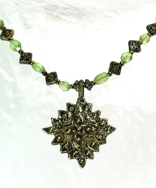 "#19813 <br>ABD bronze drop on peridot and antiqued bronze. <br>Lobster claw clasp and 4"" extender chain.<br>Alice Bailey Designs signature tag.<br>15.5"" to 19"" Limited Edition $95.00"