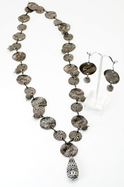 "#22219<br>Stamped gunmetal chain<br>And gunmetal coild beads.<br>With antiqued silver filigree drop.<br>32"" Limited Edition.<br>Necklace $99.00<br>Earrings $29.00"