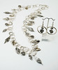 """#10717 <br>Pewter leaves on silver plated multi-loop chain. <br>Magnetic clasp. <br>Wear necklace at 36"""" (as shown) or doubled at 18"""" Limited Edition $150.00<br>Earrings not available."""