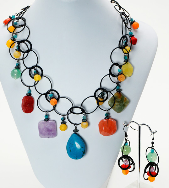 "#24418<br>Turquoise, amethyst,antique jade, strawberry<br> Quartz, Serpentine, hematite and glass.<br>On matte black multi-loop chain.<br>Matte black clasp<br>And 4"" extender chain.<br>17"" to 21"" Limited Edition.<br>Necklace $175.00<br>Earrings$40.00"
