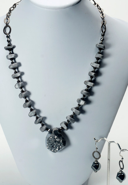 """#13020<br>Silver quartz druzy pendant<br>On hematite.<br>Gunmetal chain, clasp<br>And 4"""" extender chain.<br>17.5"""" to 21.5"""" Limited Edition.<br>Necklace $99.00<br>Earrings $27.00"""