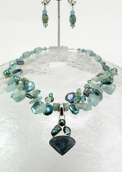 """#15812 Aqua marine drusy, green amethyst, pearl and sterling silver pendant on aqua marine, pearl, angelite and Swarovski crystal. Sterling silver and blue topaz clasp and 3"""" heavy sterling silver extender chain. <br> .Alice Bailey Designs signature tag.<br>16 1/2 """" to 19 1/2 """" One-of-a-kind.<br><br><a href=""""https://www.paypal.com/cgi-bin/webscr?cmd=_cart&amp;add=1&amp;business=alice@AliceBaileyDesigns.com&amp;item_name=Alice%20Bailey%20Designs%20Item%20Number%15812%20Necklace&amp;item_number=15812&amp;amount=%24675.00&amp;return=http://www.paypal.com&amp;cancel_return=http://www.paypal.com"""" target=""""_click"""" class=""""paypalbutton"""">Purchase Necklace $675.00</a><br><br> <br><br><a href=""""https://www.paypal.com/cgi-bin/webscr?cmd=_cart&amp;add=1&amp;business=alice@AliceBaileyDesigns.com&amp;item_name=Alice%20Bailey%20Designs%20Item%20Number%2015812%20Earrings&amp;item_number=15812&amp;amount=%2455.00&amp;return=http://www.paypal.com&amp;cancel_return=http://www.paypal.com"""" target=""""_click"""" class=""""paypalbutton"""">Purchase Earrings $55.00</a><br><br> <br><br><a href=""""https://www.paypal.com/cgi-bin/webscr?cmd=_cart&amp;add=1&amp;business=alice@AliceBaileyDesigns.com&amp;item_name=Alice%20Bailey%20Designs%20Item%20Number%2015812%20Earrings%20and%20Necklace&amp;item_number=15812&amp;amount=%24730.00&amp;return=http://www.paypal.com&amp;cancel_return=http://www.paypal.com"""" target=""""_click"""" class=""""paypalbutton"""">Purchase Necklace and  Earrings $730.00</a><br><br> <br><br><br><br><img src=""""http://ali.smugmug.com/Other/WebSiteImages/i-BftLFq2/0/O/paypal-175-50-O.jpg""""><br><font class=""""captionfooter"""">Free Shipment on all Orders</font>"""