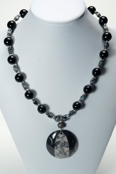 "#12620<br>Ammonite fossil,<br>Snowflake obsidian and glass.<br>Silver plated clasp<br>And 4"" extender chain.<br>17"" to 21"" Limited Edition.<br>$95.00"