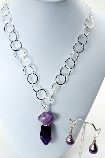 "#15117 <br>Amethyst drop on silver plated clasp and chain.<br>Necklace 20"" or less. Limited Edition $75.00<br>Earrings with silver plated French clips $26.00"