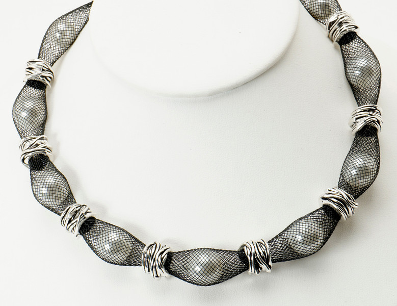 "#17319<br>White glass pearls caged<br>In nylon, with pewter. <br>Silver plated clasp and 4"" extender chain.<br>16"" to 20"" Limited Edition.<br>$95.00"