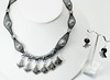 "#14314<br>Hammered pewter tube, beads<br>and caged white glass pearls<br>In black nylon.<br>Silver plated clasp and 4""extender chain.<br>Necklace 16"" to 20"" Limited Edition. $95.00<br>Earrings with silver ear wires $25.00"