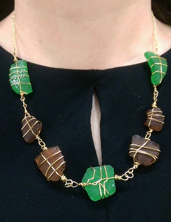 Necklace of green and brown pieces of frosty-looking sea glass linked via gold wire wraps and jump rings
