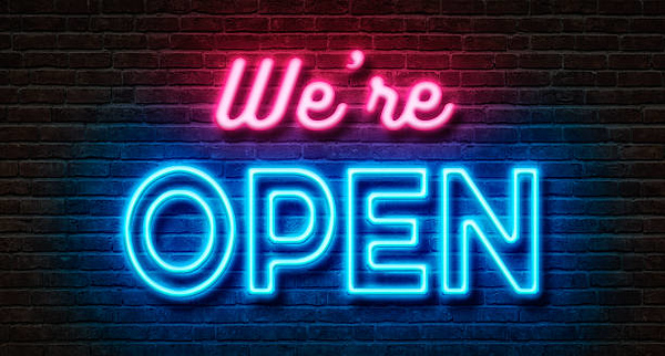 Neon sign on a brick wall - We are open