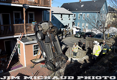 BOSTON MARCH 15:  Boston Firefighters look over the scene where an SUV jumped a parking area and into the building next door,  Sunday March 15, 2020, in East Boston. The accident happened on Falcon Street, the occupants of the vehicle were able to exit the vehicle before the fire department arrived.  (Jim Michaud / MediaNews Group/Boston Herald)
