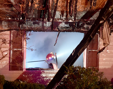 A South Windsor firefighter works on the first floor of a home after the heavy fire was knocked down,  Sunday, January 15, 2017, on Griffin Road in South Windsor. The fire was reported just before 8pm by a neighbor. The fire destroyed the two-story home, no one was injured but there were reports of pets possibly in the home. (Jim Michaud / Journal Inquirer)