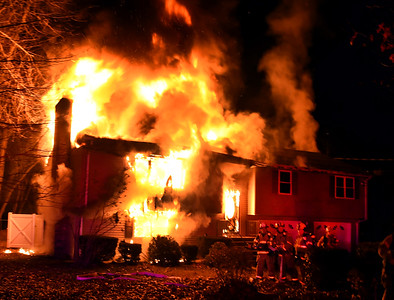 South Windsor firefighters wait for their hoses to be charged with water as fire engulfs a home, Sunday, January 15, 2017, on Griffin Road in South Windsor. The fire was reported just before 8pm by a neighbor. The fire destroyed the two-story home, no one was injured but there were reports of pets possibly in the home. (Jim Michaud / Journal Inquirer)