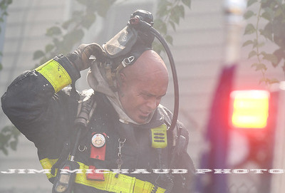 BOSTON JULY 21: A Boston pulls off his head gear as first due firefighter takes a break as firefighters struggled in the 95 degree heat fighting a 5-alarm fire on Quincy Street in Dorchester, Sunday, July 21, 2019, in Roxbury. (Jim Michaud / MediaNews Group/Boston Herald)