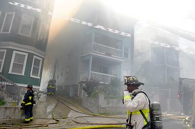 BOSTON JULY 21: Boston firefighters struggle in the 95 degree heat battling a 5-alarm fire on Quincy Street in Dorchester, Sunday, July 21, 2019, in Roxbury. (Jim Michaud / MediaNews Group/Boston Herald)