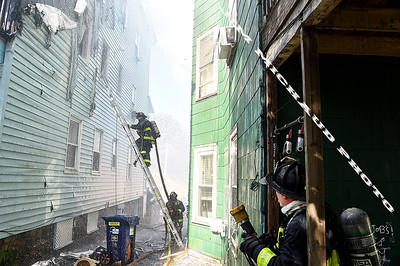 BOSTON JULY 21: Boston firefighters struggle in the 95 degree heat battling a 5-alarm fire on Quincy Street in Dorchester, Sunday, July 21, 2019, in Roxbury. (Jim Michaud / MediaNews Group/Boston Herald)