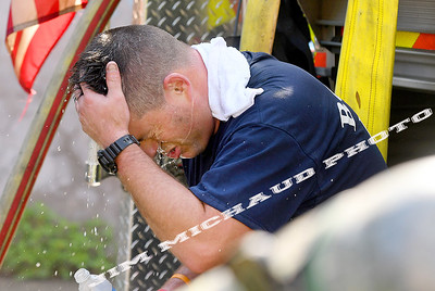BOSTON JULY 21:  Boston firefighter Charlie Bero with Engine 20, one of the first due firefighters, pours water over his head as firefighters struggled in the 95 degree heat fighting a 5-alarm fire on Quincy Street in Dorchester, Sunday, July 21, 2019, in Roxbury. (Jim Michaud / MediaNews Group/Boston Herald)