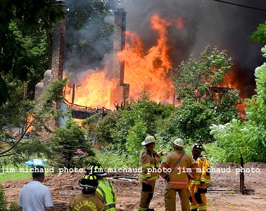 Firefighters including Ellington fire chief Jack Rich II, white hat center, look on at a house fully involved in fire, Saturday, July 11, 2020, in Ellington. The fire was reported just before 1pm at 160 Porter Street in Ellington. Rich said he struck the second alarm as he drove down RT140 from East Windsor where he was teaching a fire class. Rich said once he saw the smoke column in the air he new he had a major fire. Rich said the entire house was engulfed in flames when he arrived. The home was located up a hill and well off the road making it difficult to access and to get water to. Firefighters had to be relieved frequently due to the heat and humidity Saturday. Several mutual aid tankers were called to supply water to portable ponds that were set up to supply the water delivered by the tankers. Given the heavy volume of fire and other difficulties the house was a total loss. Rich said the fire must have burned for a while before being spotted in the rural location off of Kibbe Road not far from the Ellington Airport. No one was injured in the blaze but 11 people living in the home were displaced. The fire is being investigated by the Ellington fire marshal's office. No injuries were reported. (Jim Michaud / Journal Inquirer)