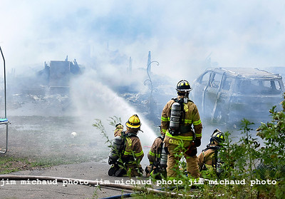 Firefighters dose the burning house with water that was fully involved in fire when they arrived, Saturday, July 11, 2020, in Ellington. The fire was reported just before 1pm at 160 Porter Street in Ellington. Ellington Fire Chief Jack Rich II said he struck the second alarm as he drove down RT140 from East Windsor where he was teaching a fire class. Rich said once he saw the smoke column in the air he new he had a major fire. Rich said the entire house was engulfed in flames when he arrived. The home was located up a hill and well off the road making it difficult to access and to get water to. Firefighters had to be relieved frequently due to the heat and humidity Saturday. Several mutual aid tankers were called to supply water to portable ponds that were set up to supply the water delivered by the tankers. Given the heavy volume of fire and other difficulties the house was a total loss. Rich said the fire must have burned for a while before being spotted in the rural location off of Kibbe Road not far from the Ellington Airport. No one was injured in the blaze but 11 people living in the home were displaced. The fire is being investigated by the Ellington fire marshal's office. No injuries were reported. (Jim Michaud / Journal Inquirer)