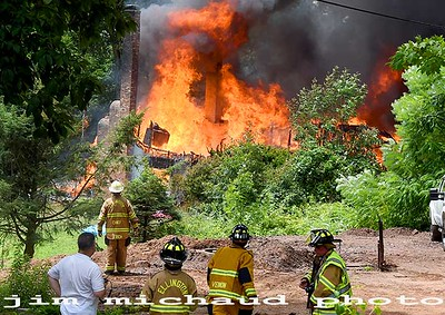 Firefighters including Ellington fire chief Jack Rich II, closest to the fire, look on at a house fully involved in fire, Saturday, July 11, 2020, in Ellington. The fire was reported just before 1pm at 160 Porter Street in Ellington. Rich said he struck the second alarm as he drove down RT140 from East Windsor where he was teaching a fire class. Rich said once he saw the smoke column in the air he new he had a major fire. Rich said the entire house was engulfed in flames when he arrived. The home was located up a hill and well off the road making it difficult to access and to get water to. Firefighters had to be relieved frequently due to the heat and humidity Saturday. Several mutual aid tankers were called to supply water to portable ponds that were set up to supply the water delivered by the tankers. Given the heavy volume of fire and other difficulties the house was a total loss. Rich said the fire must have burned for a while before being spotted in the rural location off of Kibbe Road not far from the Ellington Airport. No one was injured in the blaze but 11 people living in the home were displaced. The fire is being investigated by the Ellington fire marshal's office. No injuries were reported. (Jim Michaud / Journal Inquirer)