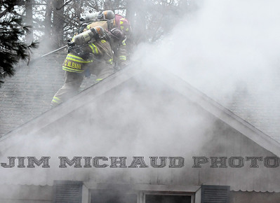 South Windsor firefighters work opening the roof of a burning house fire, Tuesday, January 8, 2019, in South Windsor. The fire came in around 4pm at 234 Long Hill Road when a passing motorist noticed smoke coming from the house. Three dogs escaped when police arrived and opened the door. The three cats were removed by firefighters, 2 responded quickly to the oxygen they were given a third seemed to be unconscious as firefighters continued to work on him. The house sustained heavy damage to the kitchen and living room, the area around a wood stove sustained the heaviest damage, Chief Kevin Cooney said. The house was deemed uninhabitable and the residents are staying with other family members Cooney said. (Jim Michaud / Journal Inquirer)