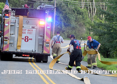 firefighters work laying a hose as the South Windsor firefighter department does a drill, Tuesday, July 24, 2018, in South Windsor. The drill took place on Niederwerfer Road where fire hydrants only cover part of the area. Fire firefighters laid 5 inch large diameter hose called a supply line. That line feeds water to the fire engines during a fire. Firefighters had to lay over 1,500 feet of supply line off of their brand new engine 6 that has not gone into service yet. (Jim Michaud / Journal Inquirer)
