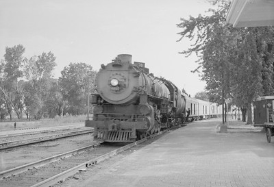 2016.020.98.049--jim neubauer 828 neg--UP--steam locomotive 7002 on passenger train 70 arriving--Manhattan KS--c1953 0700