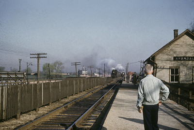2016.020.01.1955-027--jim neubauer 35mm kodachrome--C&NW--two eastbound steam commuter passenger trains approaching depot--Avondale IL--1955 0400
