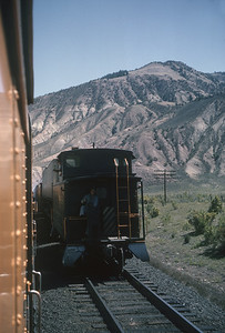 2016.020.26.25--jim neubauer 35mm kodachrome--D&RGW--view of caboose on hind end of freight train from passenger train vestibule--location unknown--1963 0900