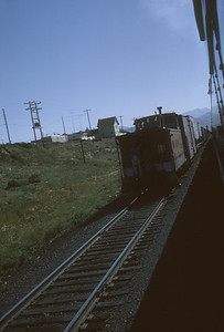2016.020.26.17--jim neubauer 35mm kodachrome--D&RGW--caboose on hind end of freight train as seen from passenger train--location unknown--1963 0900