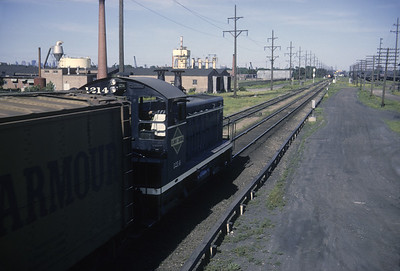 2016.020.04.14--jim neubauer 35mm kodachrome--ICRR--EMD diesel switcher locomotive 1214 at BRC crossing with Lond-O-Corn approaching--Hawthorne IL--1965 0600