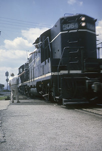 2016.020.04.04--jim neubauer 35mm kodachrome--ICRR--EMD diesel locomotive 9064 on freight train hooping up orders action--Broadview IL--1963 0727