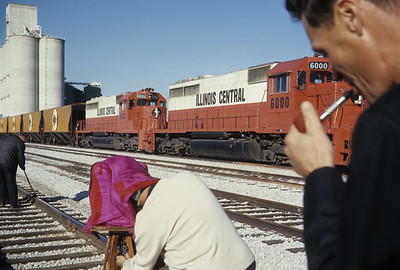 2016.020.04.25--jim neubauer 35mm ektachrome--ICRR--company photographer photographing track oiler while trainmaster looks on--location unknown--1968 1100