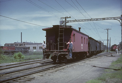 2016.020.16.05--neubauer 35mm kodachrome--CNS&M--caboose on freight train shoving with crew--North Chicago IL--1962 0500