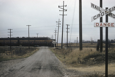 2016.020.19.04--jim neubauer 35mm kodachrome--PRR--ALCO diesel locomotive on local freight train at country crossing--Valparaiso IN--1956 1117