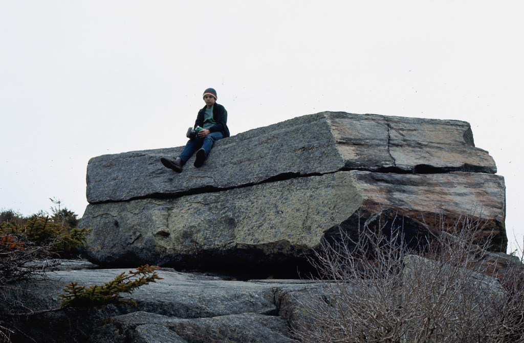 """My son, Frank Lacey, seated on the Sarcophagus ('Boat"""") - a featured attraction on Mt. Monadnock in Southern NH."""