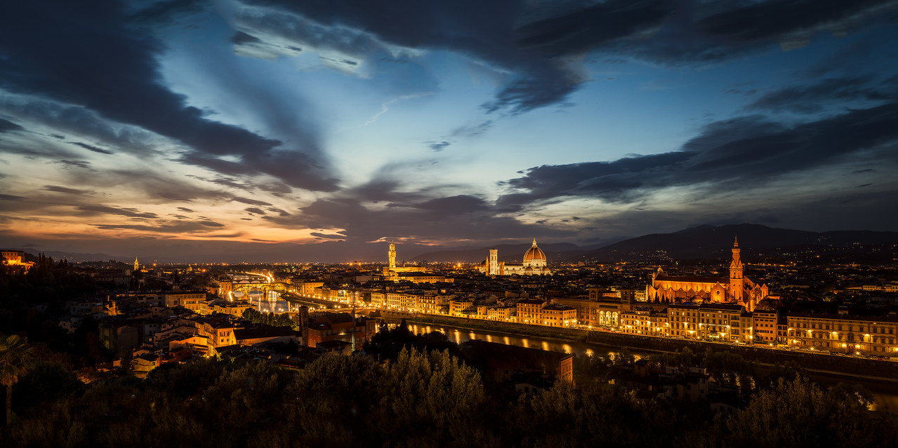 Piazzale Michelangelo is my favourite viewpoint of Florence. Every afternoon, hoards of people come to catch a glimpse of the sun setting over the Fiume Arno and the various bridges over the river.<br /> <br /> This photo is a five photo panorama, stitched in photoshop and captures the contrasts between the sunset, city lights and shadows.