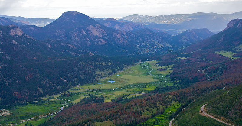There is a lot to see in this photo. This is the Fall River valley Rocky Mountain National Park. In the lower left is the rocks of the Alluvial Fan from the 1982 Lawn Lake flood. Estes Park is at the end of the valley. Trail Ridge Road can be seen winding it's way up.