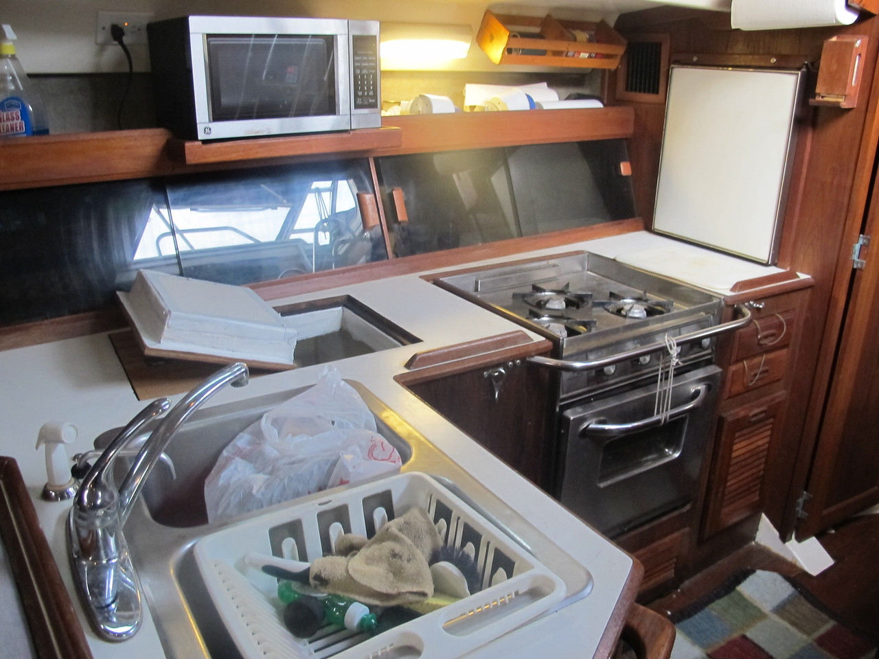 Galley with pressurized hot and cold water, propane oven, icebox, fridge, and microwave.