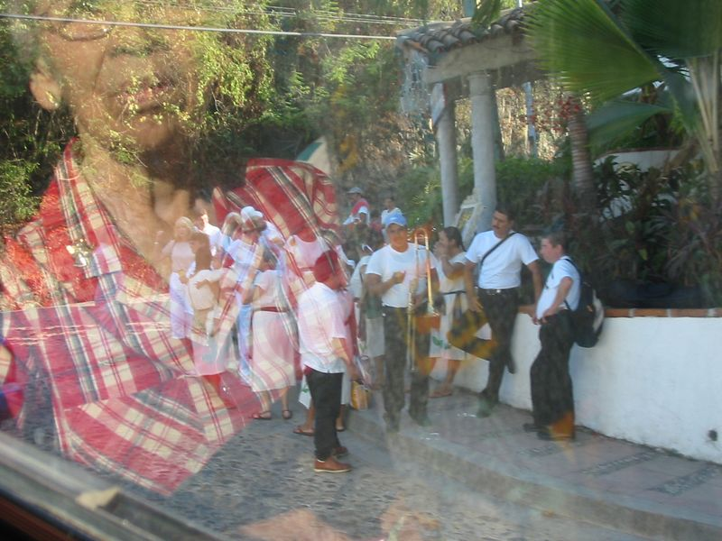 People getting ready for a procession (reflection of woman on bus)