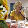 Jocelyn Allore, who volunteers twice a week at the reception desk of the Dracut was working hard on Wednesday morning answering phones and helping members. SUN/JOHN LOVE