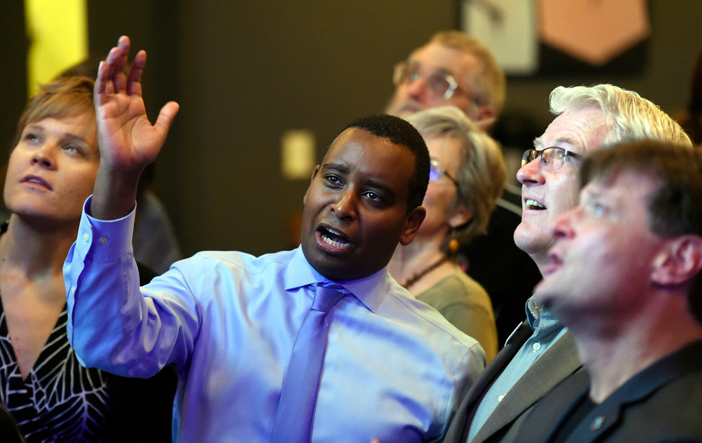 . BOULDER, CO - NOVEMBER 6, 2018: Joe Neguse, center, Matt Jones and Sam Weaver react after seeing the first-round of results during a democratic watch party at Nissi\'s Entertainment Venue and Event Center on Tuesday night in Lafayette. Neguse is running for the U.S. House of Representatives from Colorado\'s 2nd district. More photos of election night go to dailycamera.com (Jeremy Papasso/Staff Photographer)