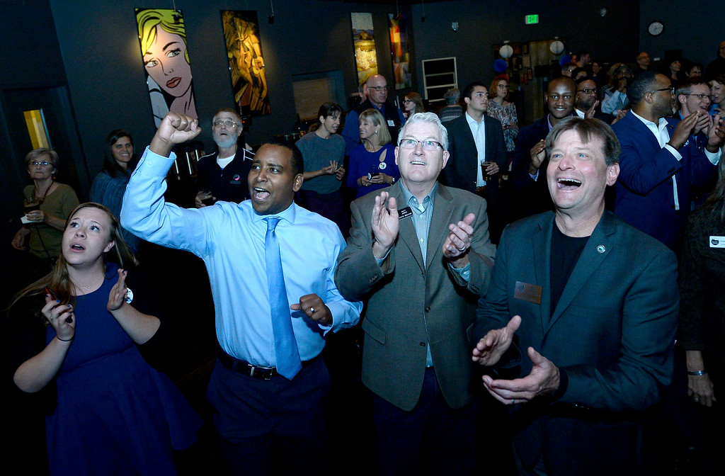. BOULDER, CO - NOVEMBER 6, 2018: Katie Wallace, left, Joe Neguse, Matt Jones and Boulder City Council member Sam Weaver react after seeing the first-round of results during a democratic watch party at Nissi\'s Entertainment Venue and Event Center on Tuesday night in Lafayette. Neguse is running for the U.S. House of Representatives from Colorado\'s 2nd district and Jones is running for Boulder County Commissioner. More photos of election night go to dailycamera.com (Jeremy Papasso/Staff Photographer)