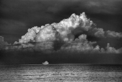 A storm approaching as a small ship returns to the harbor in Manila.
