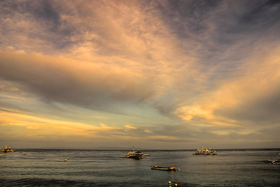 Small fishing boats anchored after a day of work in Santander, Philippines
