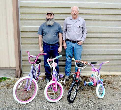 Thomas Beesley, left, and Joe's Car Care owner Joe Luchtefeld, right, have four bikes ready for a scheduled delivery for Christmas. Charles Mills photo