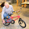 Joe Luchtefeld owner of Joe's Car Care of Altamont makes some final adjustments to a bicycle before he gives it away. Luchtefeld has given away over 150 bicycles since mid-summer. Charles Mills photo