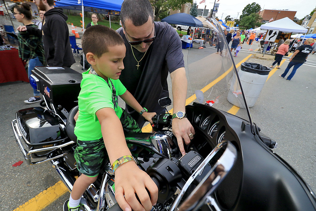 . The 25th anniversary of the Johnny Appleseed Festival was held on Saturday in downtown Leominster, September 22, 2018. Holden Riveria, 7, and his dad Robert Rivera both of Leominster look over a police motorcycle on display at the festival. SENTINEL & ENTERPRISE/JOHN LOVE