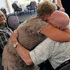 Roger Schneider | The Goshen News<br /> Carole Yoder gives Farrell Cripe a hug during the final Johnson Controls retirees club reunion Saturday. Looking on is Cliff Holdread.